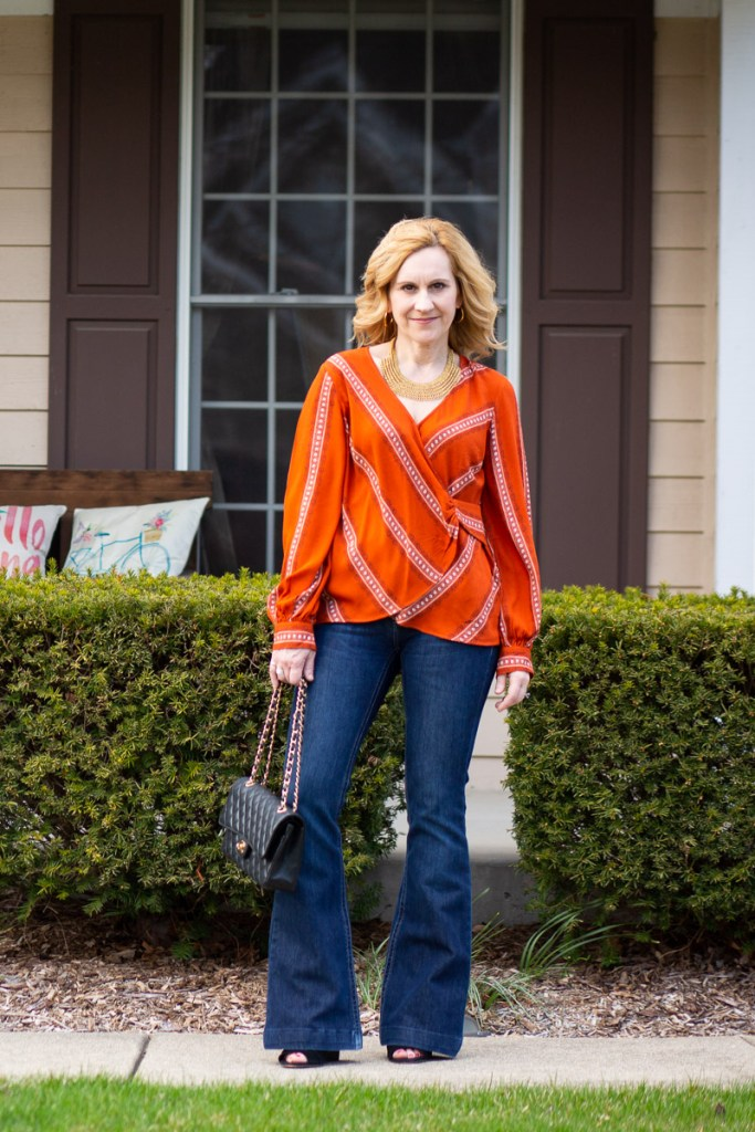 Styling an orange printed blouse with dark wide leg jeans.