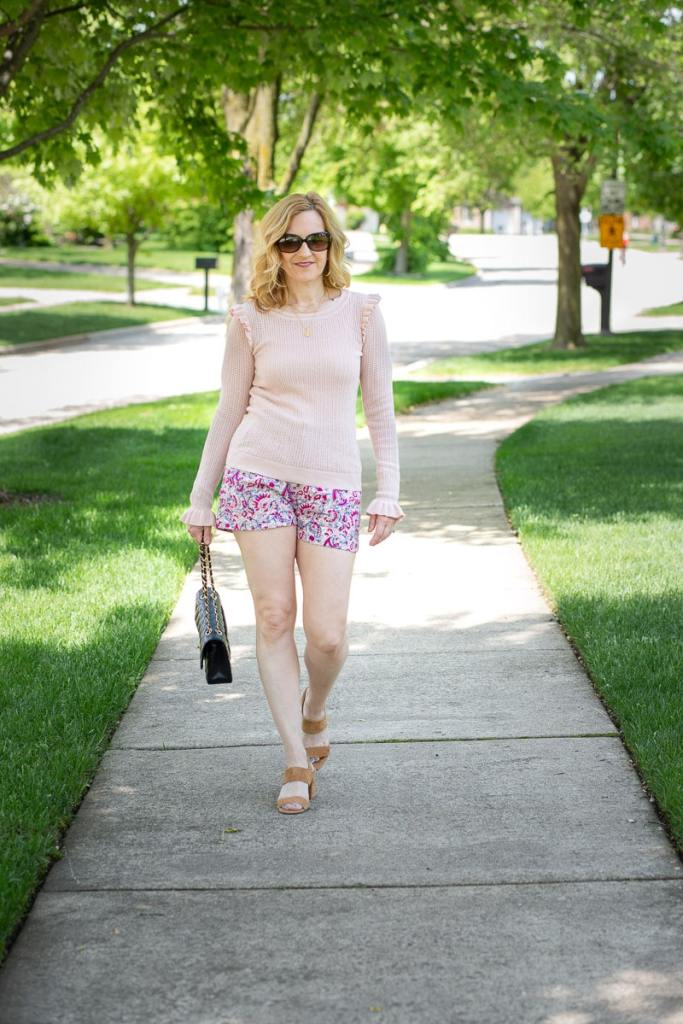 A chic early summer look featuring printed shorts and sheer ruffled sweater.