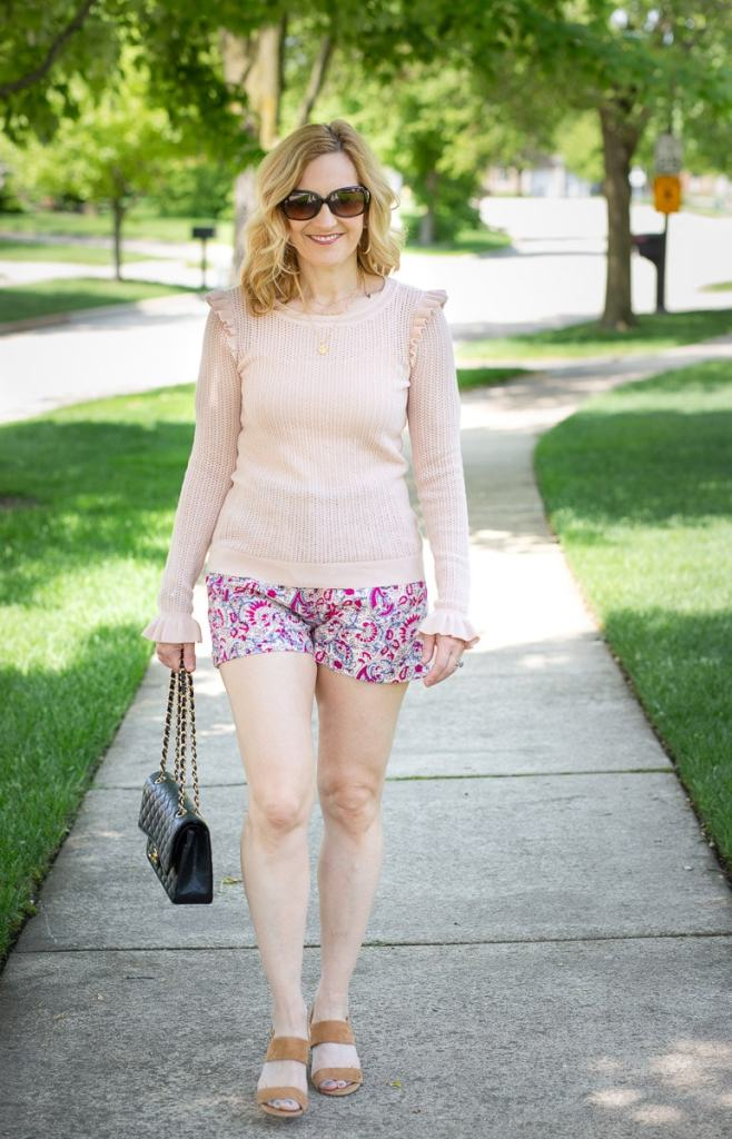 Dressing up paisley shorts with a sheer ruffled pink sweater.