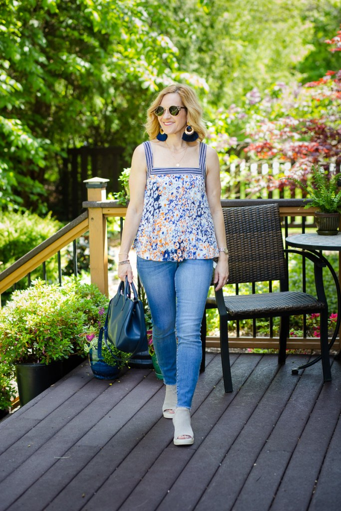A printed floral tank paired with light skinny jeans and wedges.