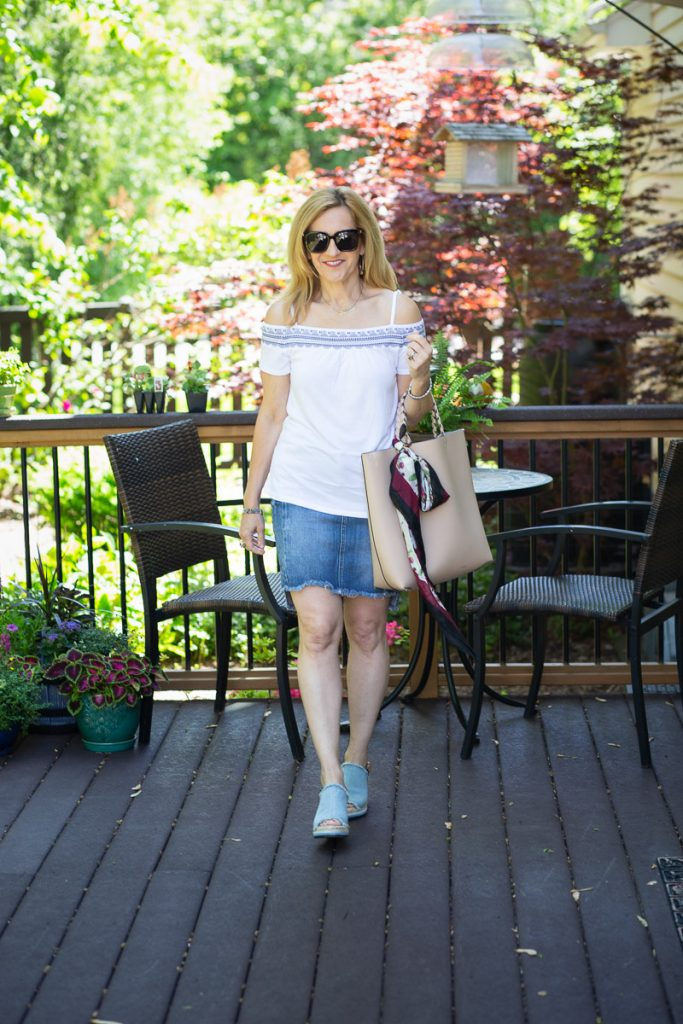 A summer chic look featuring a white off the shoulder top paired with a denim skirt.