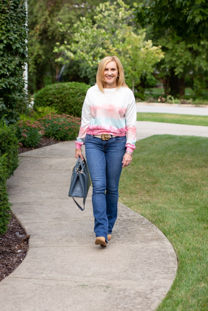 A casual fall look that features a tie dye sweatshirt and jeans.