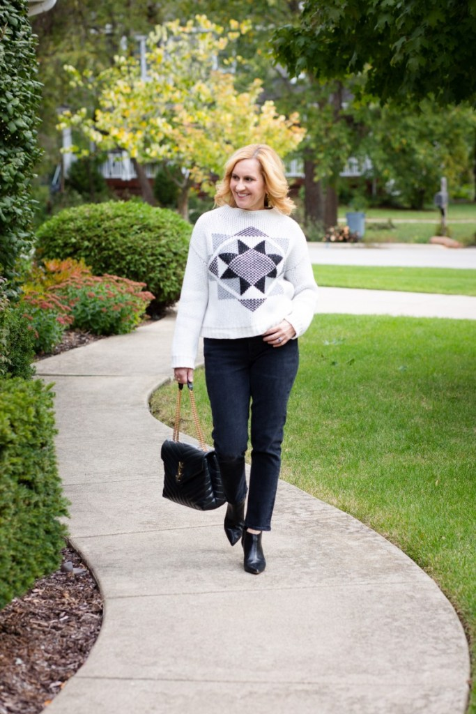A cozy chic fall look that features a star sweater paired with cropped black jeans that were rented from Nuuly.