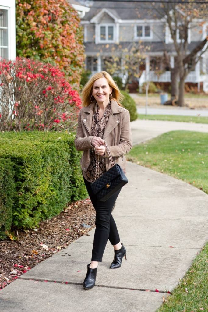 Pairing a snakeskin bow top with a suede jacket and black skinny pants.
