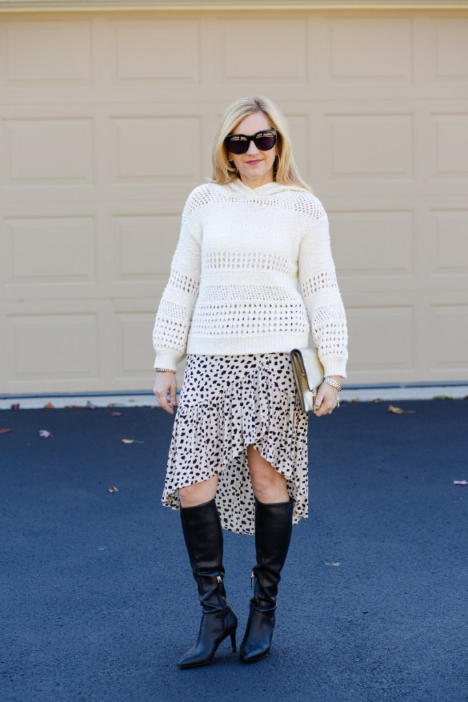 An all white look featuring a hoodie sweater and high low ruffle skirt.