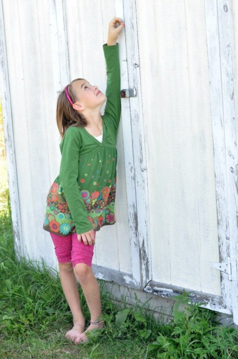 Girl reaching hand up high by old shed by Katie M. Reid Photography