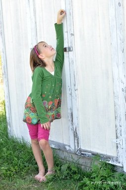 Girl looking up next to a whitewashed shed in Spring by Katie M. Reid Photography