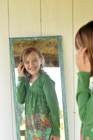 Girl looking in mirror and smiling by Katie M. Reid photography