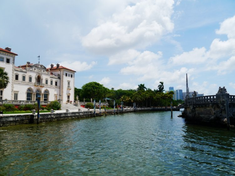 Image of italian-style mansion Vizcaya next to the waterside with Miami skyline in the background