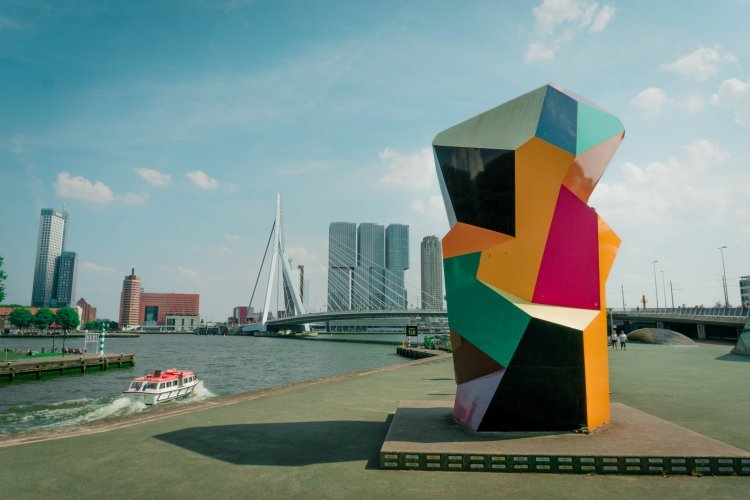 Image of Rotterdam waterfront and erasmus bridge with colourful sculpture in foreground