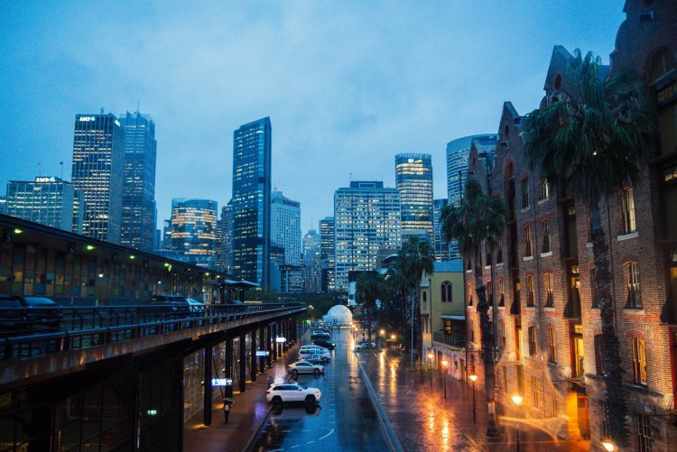Image of sydney city skyline at dusk with artificial light reflected in rain on pavements