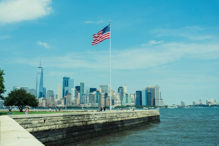 Image of New York City skyline across the water with US flag pole in foreground