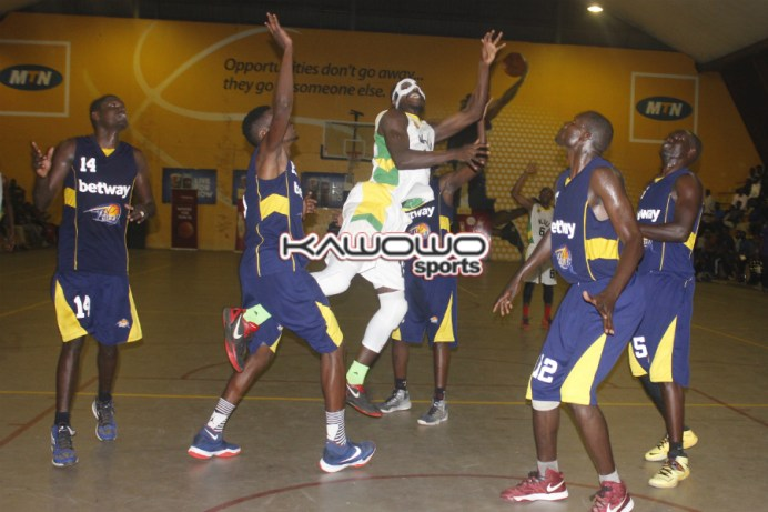 KIU's Ivan Lumanyika goes for a basket in the forest of Power players during Game 2.