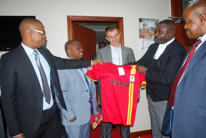 A delegation from FUFA led by the president Moses Magogo hands over a Uganda Cranes jersey to deputy speaker of parliament Jacob Olanya