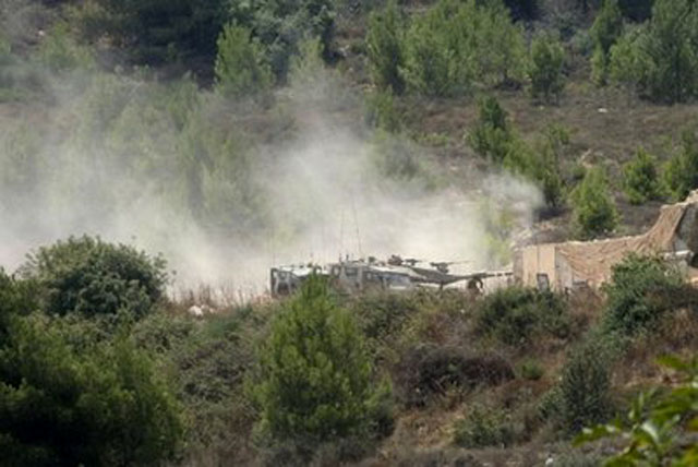 Israeli vehicles patrol an area near the site of an exchange of fire between Israeli and Lebanese troops along the border between Israel and Lebanon, seen from the southern border village of Adaisseh, Lebanon, Tuesday, Aug. 3, 2010. Lebanon and Israeli troops exchanged fire on the border Tuesday in the most serious clashes since a fierce war four years ago. Pic. Credit: AP - Lutfallah Daher