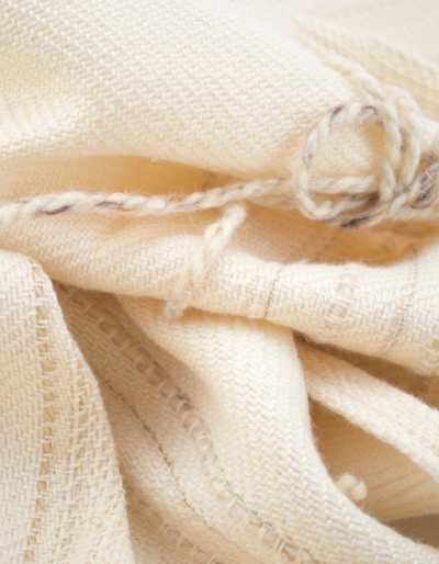 Throw blanket created with pinkish beige silk, ivory cashemeres, unbleached wool, plus a few linen threads and beige cotton slipped into the throw. Graphic wool flowers of beige country, added by hand, after weaving.  Technique: Throw blanket hand-woven in a traditional way on non-mechanical looms in the 7th arrondissement of Paris in France.  Finishes: Right edge. Double stitching.4 pompoms of silk and cashmere of 5,91 inches long.  Size: 55,12 x 66,93 inches.  Single piece / 1 copy only.
