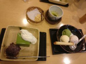 One  square plate of matcha cake with cream and bean paste, a bowl with three scoops of ice cream