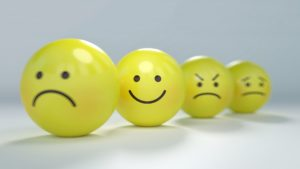 four yellow balls with sad, happy, angry, and worried faces