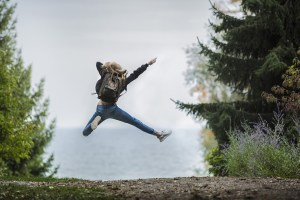 woman with backpack jumping for joy