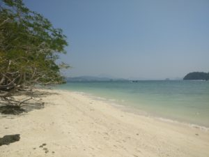 white beach with pale blue water