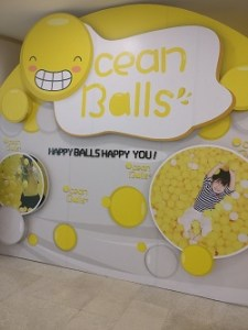 "A white and yellow sign reading""Ocean Balls! Happy balls happy you!"""