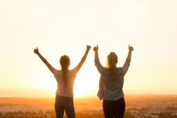 silhouette of two women with hands in the air in celebration facing a sunset