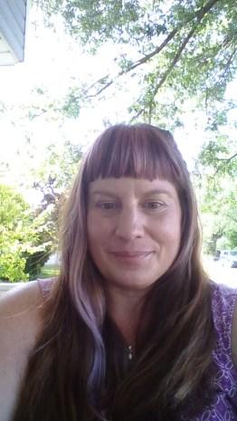 Jill Heteric smiling under a tree