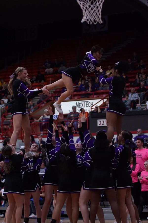 The+cheer+team+performs+a+stunt+during+a+timeout+at+the+state+basketball+tournament.+
