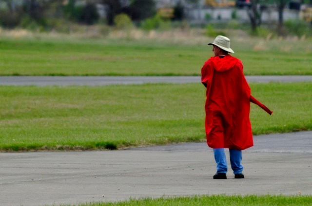 Lance Hamilton dons his red pancho at rain falls intermittently during Heat 1.