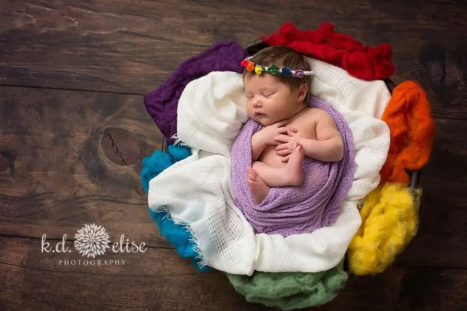 Rainbow baby surrounded by rainbow fluff by Colorado Springs newborn photographer K.D. Elise Photography.