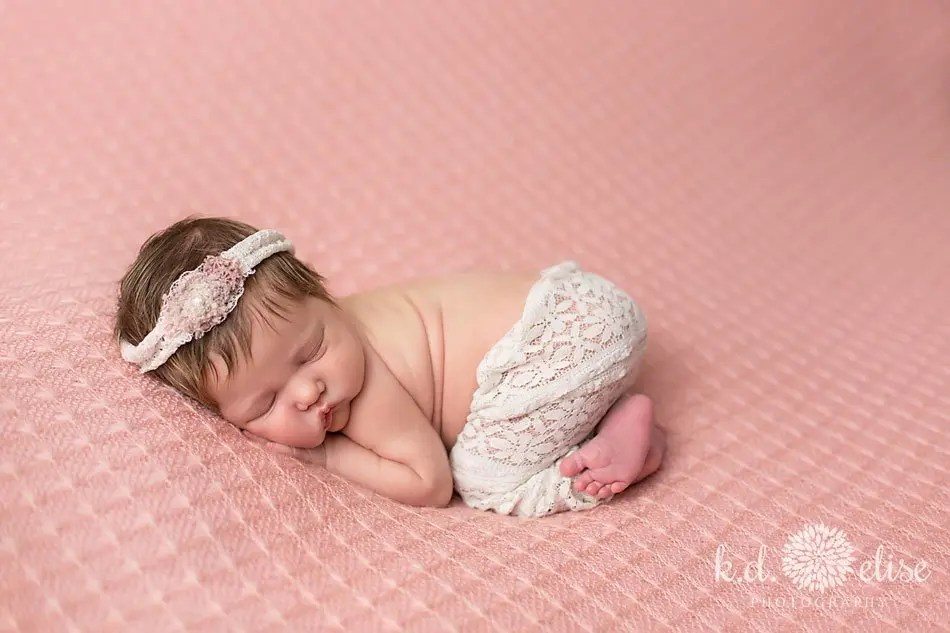 Sleeping baby on pink backdrop. Photo by K.D. Elise Photography a Colorado Springs area newborn photographer.