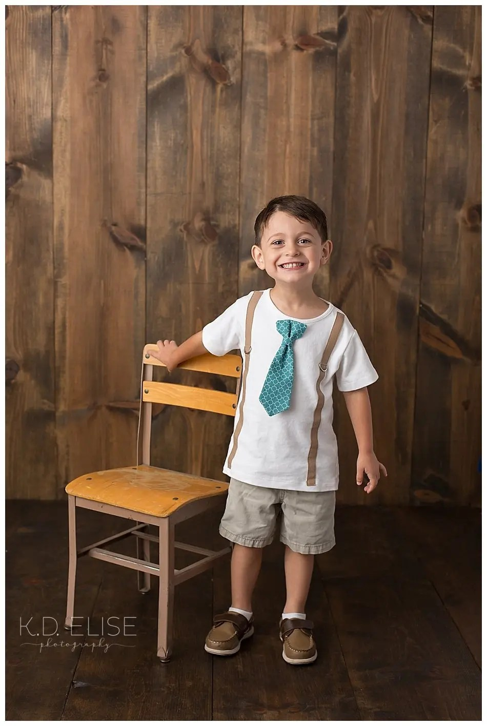 Smiling little boy in a tie shirt standing next to a wooden chair.