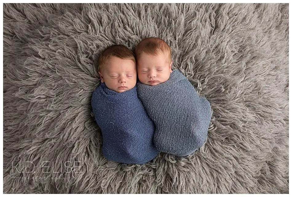 Twin newborn boys wrapped in blue laying on a grey fur.