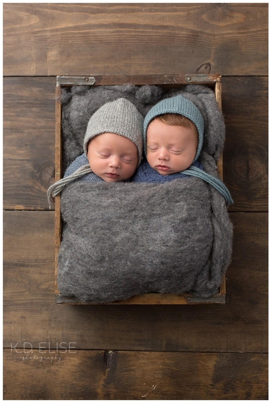 Newborn twin boys laying in a wooden crate, wrapped in grey fur.