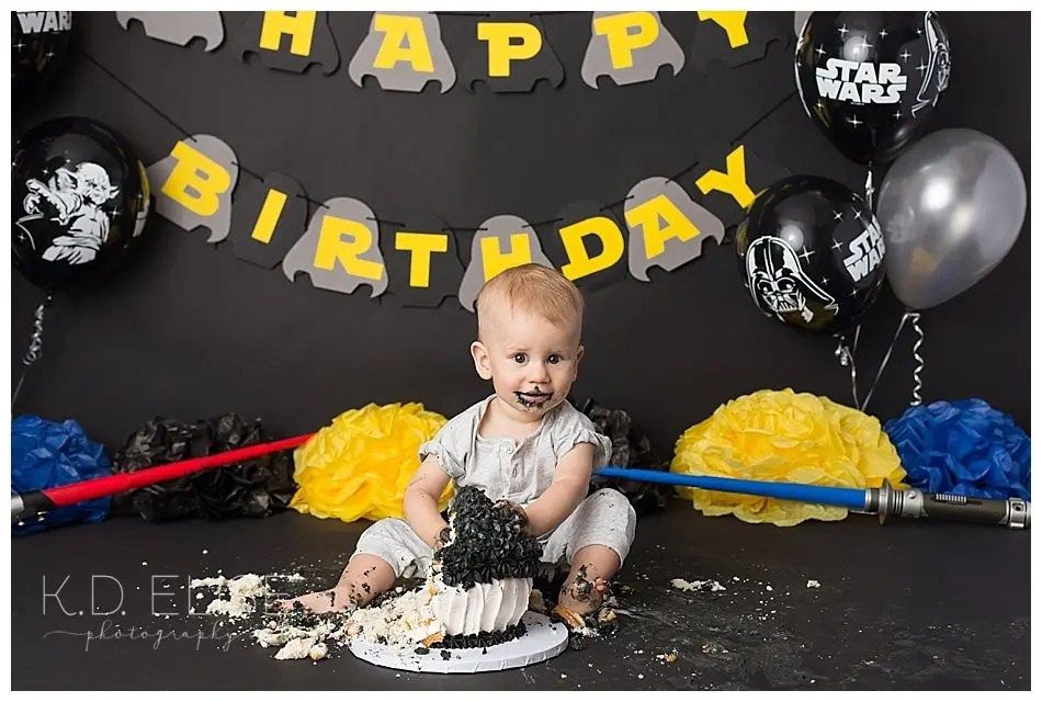 Boy eating cake and making a mess during his Star Wars themed first birthday cake smash.