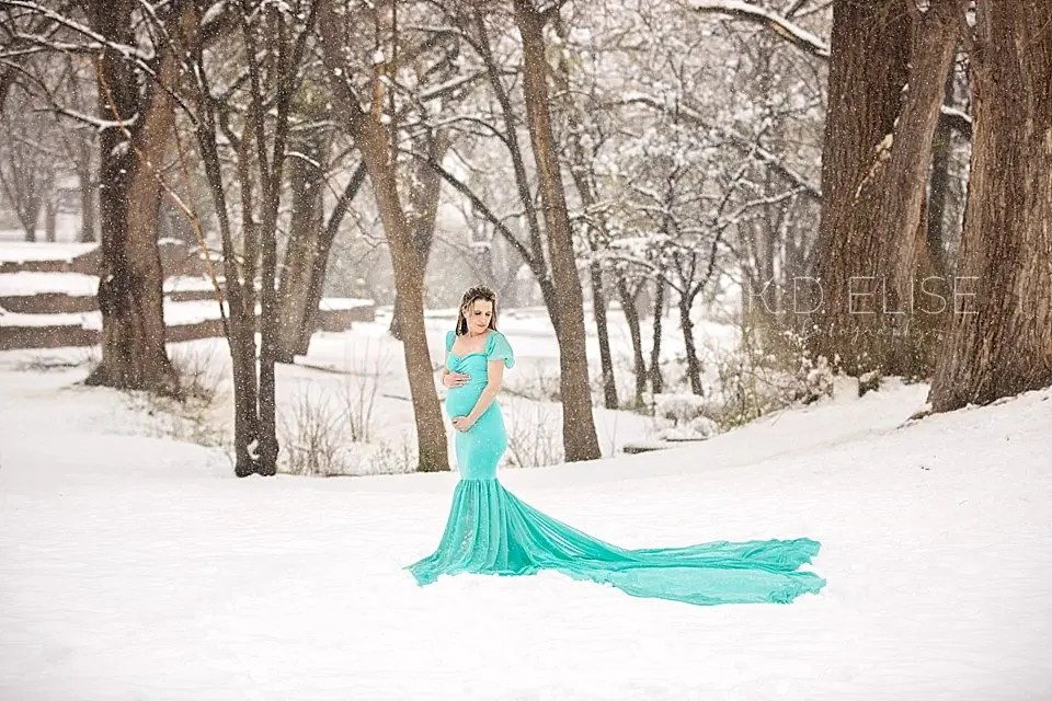 Snowy maternity photo of pregnant mom in a snow covered forest at City Park in Pueblo, CO.