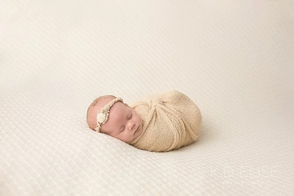 Baby girl wrapped in tan laying on a cream blanket. Photo by Pueblo photographer K.D. Elise Photography.