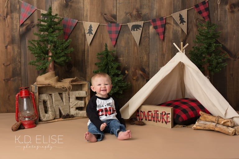 One year old boy smiles during first birthday lumberjack themed portraits.