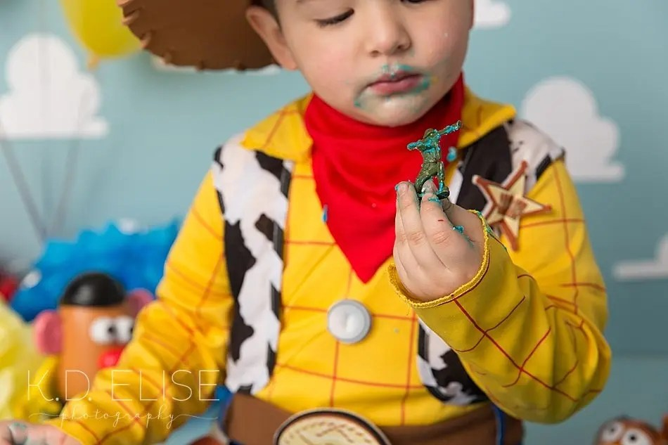 Little boy looking at a toy soldier during his cake smash with Pueblo photographer K.D. Elise Photography.