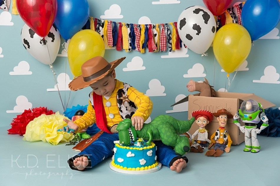 Little boy using his toy dinosaur to take a bite of birthday cake during his Toy Story themed cake smash with Colorado Springs photographer K.D. Elise Photography.