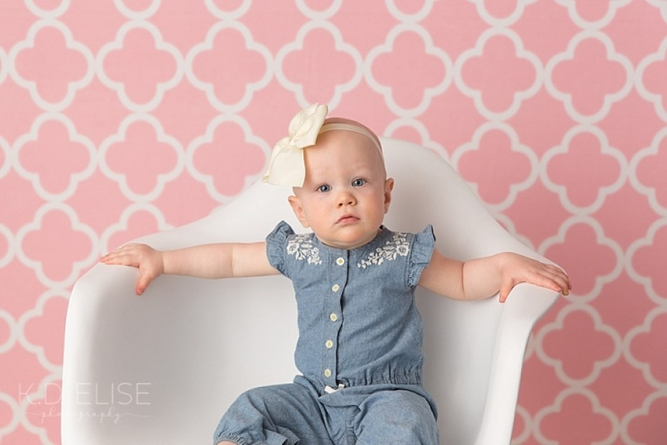 One year old baby girl in a blue outfit sitting in a white chair before her candy themed cake smash with Pueblo photographer K.D. Elise Photography.