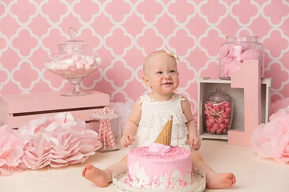Smiling baby girl with birthday cake during candy themed cake smash.