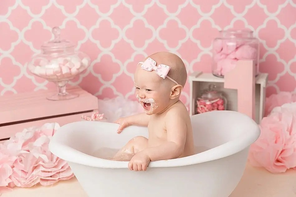 Smiling baby in a plastic clawfoot tub after candy themed cake smash.
