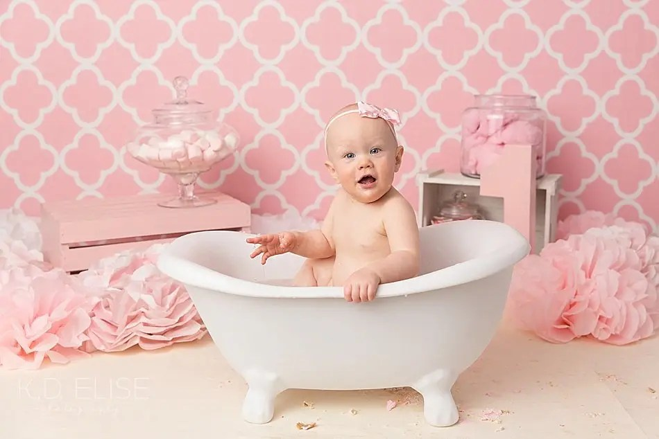 Baby girl splashing in a tub after her candy themed cake smash.