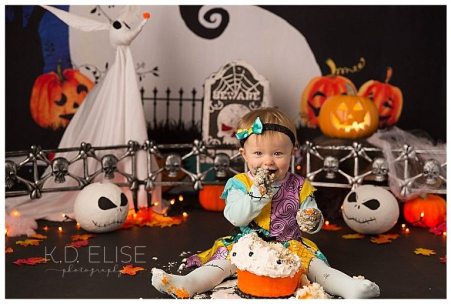 Baby girl eating cake during her Nightmare Before Christmas themed cake smash by K.D. Elise Photography