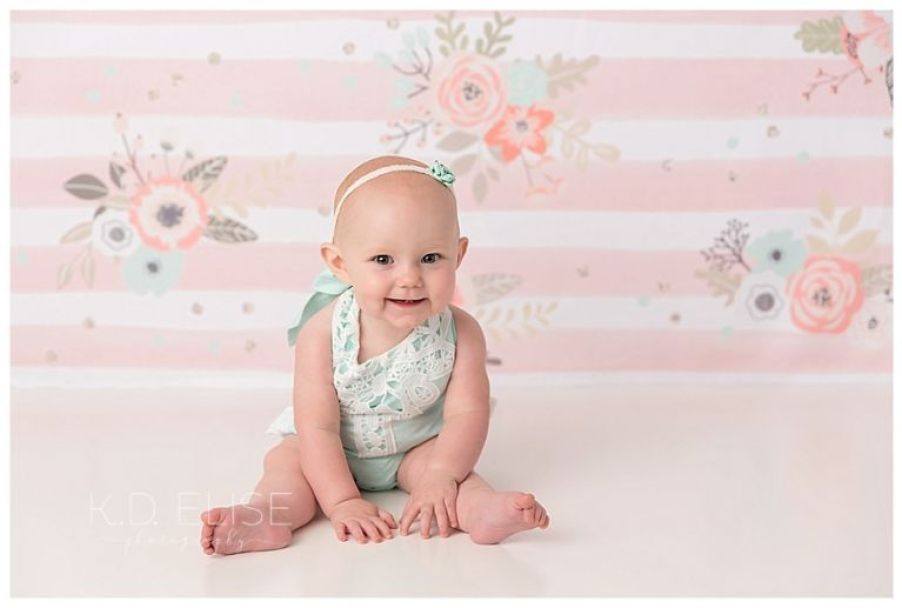Smiling baby girl in blue outfit, sitting on the floor leaning forward with a big smile.