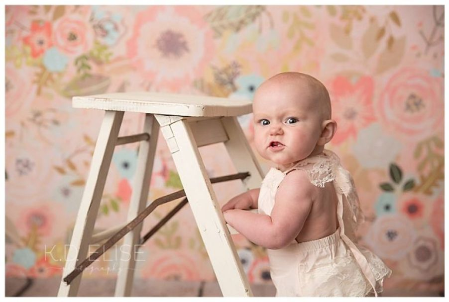 9 month milestone session of baby girl standing against a ladder in front of a floral backdrop.