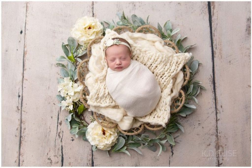 Newborn baby girl wrapped in white wrap, laying in a basket surrounded by leaves and roses.