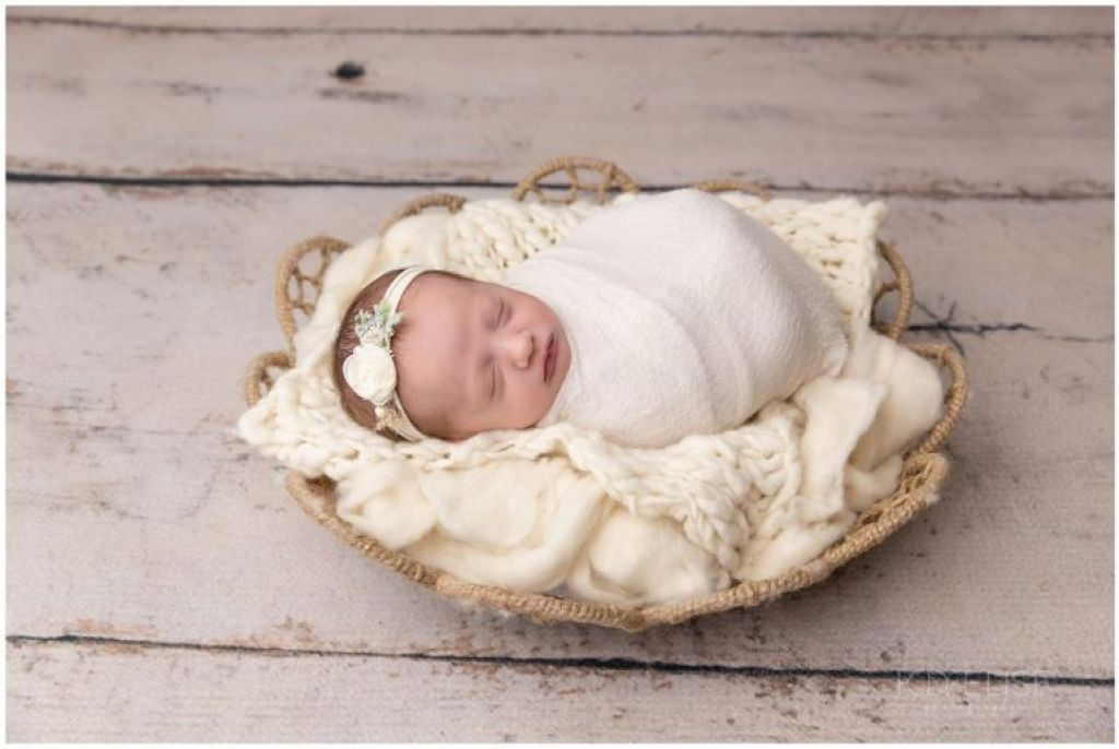 Newborn baby girl wrapped in white, laying in a basket filled with cream fur.