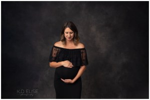 In studio maternity photography image of pregnant mom in black gown.